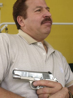 In this 2007 photo, Ruben Torres shows the gun he used to keep mass murderer William Cruse at bay 20 years earlier.