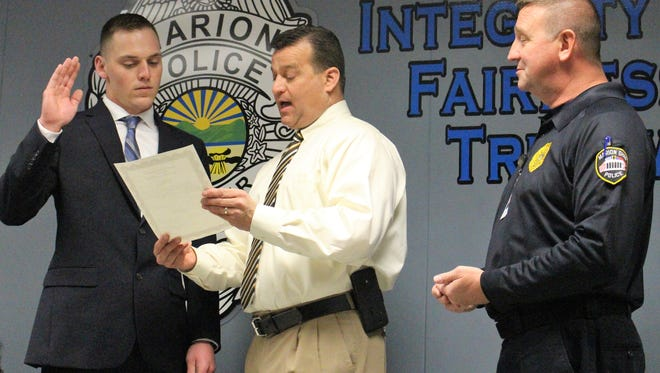Todd Bartson takes his oath to become a Marion patrol officer in front of Mayor Scott Schertzer and Chief Bill Collins on Monday.