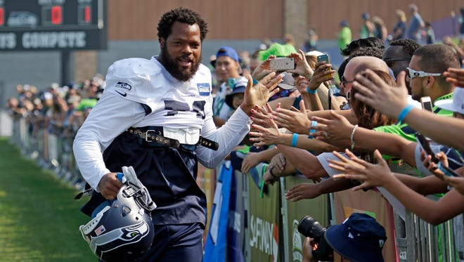 Seahawks defensive end Michael Bennett greets fans before a training camp practice on Aug. 4 in Renton. Bennett says he will remain seated on the bench during the national anthem at all the team's games this year, and he expects a backlash from fans.