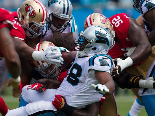 Panthers running back jonathan stewart 28 gets stopped by a trio of