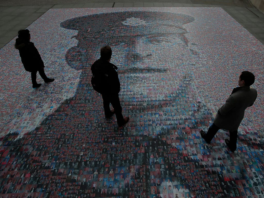 People walk across a digital mosaic of British army Pvt. Ernest Beaney, who was killed during World War I, on Nov. 7 outside BBC headquarters in London. The image of Beaney, who died in France on Aug. 8, 1916, was made up of 30,000 digital photograph