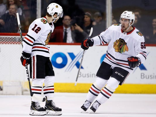 Chicago Blackhawks right wing Alex DeBrincat (12) celebrates his goal against the Arizona Coyotes with Blackhawks defenseman Erik Gustafsson (56) during the second period of an NHL hockey game Monday, Feb. 12, 2018, in Glendale, Ariz. (AP Photo/Ross D. Franklin)