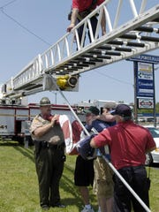 Firemen, a state trooper and volunteers fold the massive American flag that flew from a Dickson Fire Department ladder truck over Highway 46, shortly after the motorcade passed.