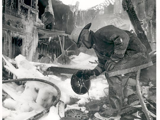 A firefighter looks through the ruins of the Frank