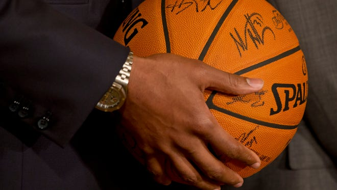 Miami Heat basketball player Chris Bosh holds a signed basketball for President Obama during an event at the White House last month.