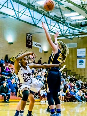 Jasmine Clerkley ,23, of Okemos puts up a successful off-balance circus shot over Courtney Sharland ,right, of Grand Ledge.