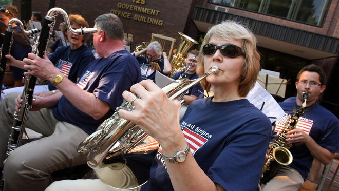 Judy Benton of Ocean City, a french horn and trumpet player for the Salisbury Community Band, takes a moment to warm-up and exercise her lips and fingers prior to the concert's start on the steps of the City Government Building in Salisbury.