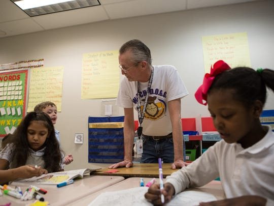 Louis Agosta, of Salisbury, helps students with their school work at Prince Street Elementary School on Monday, March 21, 2016.