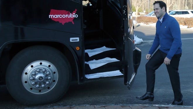 A boot-wearing Marco Rubio smiles as he gets on his campaign bus Sunday in Atkinson, N.H. (Mary Schwalm, AP)