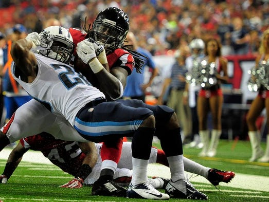 Titans running back Bishop Sankey (20) is stopped short of the goal line by Falcons defensive back Kemal Ishmael (36) during the fourth quarter at the Georgia Dome Saturday Aug. 23, 2014, in Atlanta, Ga.