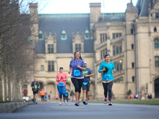 Runners pass by the Biltmore House during the 2015