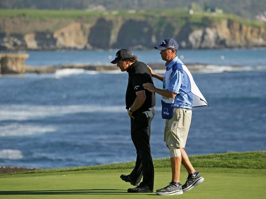 "Phil Mickelson, left, is consoled by his caddie, Jim ""Bones"" Mackay on the 18th green of the Pebble Beach Golf Links during the final round of the AT&T Pebble Beach National Pro-Am golf tournament Sunday, Feb. 14, 2016, in Pebble Beach, Calif. Vaughn Taylor won the tournament. (AP Photo/Eric Risberg)"