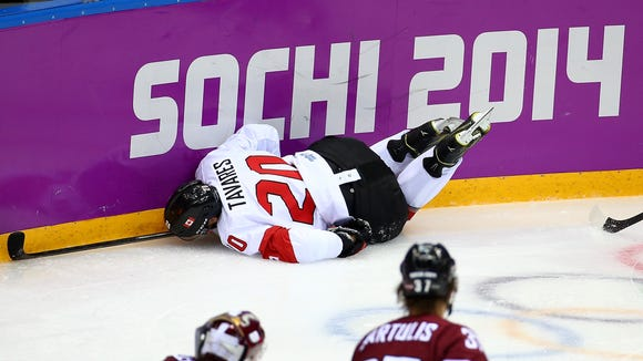 Canada's John Tavares dives into the boards during Wednesday's quarterfinal game against Latvia at the Winter Olympics in Sochi, Russia.