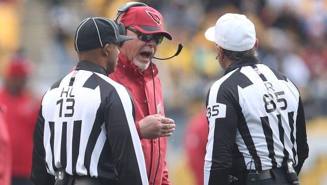 Oct. 18, 2015; Pittsburgh; Arizona Cardinals coach Bruce Arians talks with head linesman Patrick Turner (13) and referee Ed Hochuli (85) during a game against the Pittsburgh Steelers in the second quarter at Heinz Field. The Steelers won 25-13.