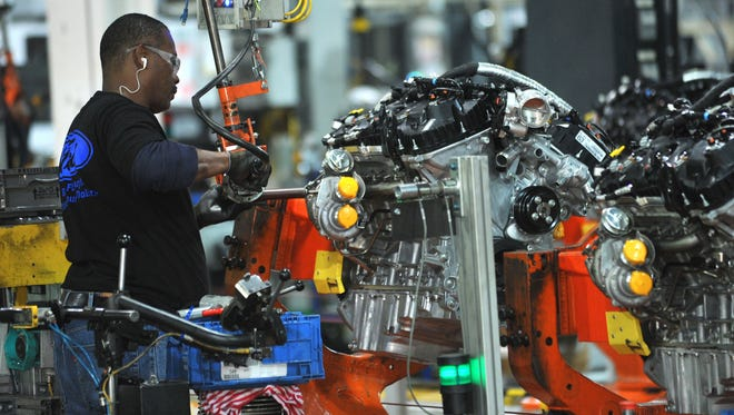A Ford employee works on an EcoBoost engine at the automaker's Cleveland Engine Plant in Brook Park, Ohio.