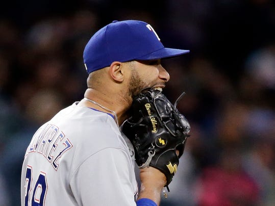 Texas Rangers relief pitcher Dario Alvarez bites on his glove as he heads back to the mound after giving up a pair of runs to the Seattle Mariners in the seventh inning of a baseball game Saturday, May 6, 2017, in Seattle. (AP Photo/Elaine Thompson)
