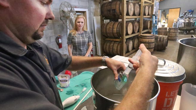 Copper Bottom Craft Distillery owner Jeremy Craig fills a small bottle with hand sanitizer while his wife and co-owner Jenni Craig looks on. When the coronavirus pandemic first took hold, the Holly Hill distillery switched to making hand sanitizer and gave it away to residents. Months into the pandemic, Copper Bottom is still making its hand sanitizer, while other distilleries around the country have stopped making the disinfectant.