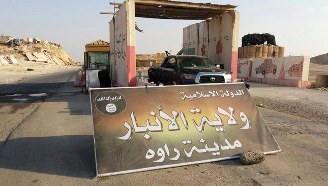 "In thisFILE - In this Tuesday, July 22, 2014, file photo, a sign is posted at a checkpoint belonging to the Islamic State group, captured from the Iraqi Army, at the main entrance of Rawah, 175 miles northwest of Baghdad, Iraq. Arabic reads, ""Islamic State, the Emirate of Anbar, City of Rawah."""