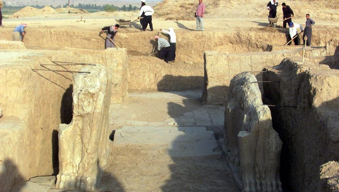 Iraqi workers clean an archaeological site in 2001 in Nimrud. The site was bulldozed by Islamic State militants Thursday, according to the government.