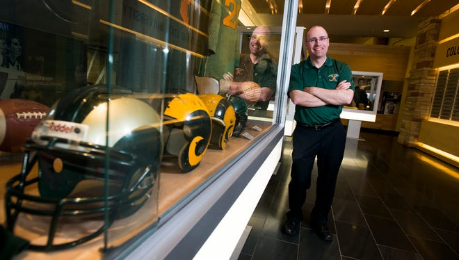 CSU athletic historian John Hirn stands alongside the football display case Thursday night in the Hall of Fame area he helped create on the south concourse of Moby Arena.