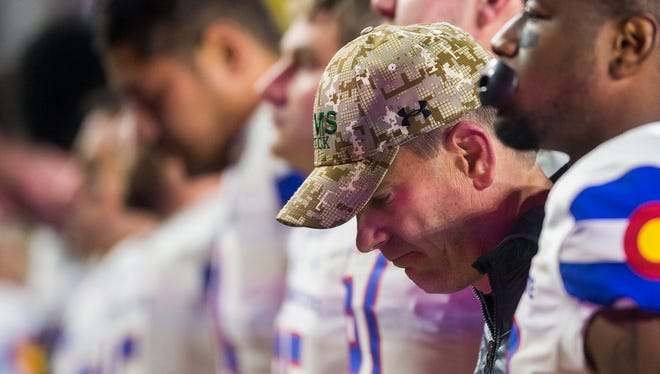 CSU coach Mike Bobo and his players lower their heads while the band plays the school's fight song early Sunday morning following an overtime loss to Boise State.