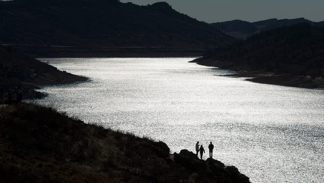 People stand along the rocks overlooking the East edge of the reservoir on Saturday morning, Nov. 18, 2017, at Horsetooth Reservoir in Fort Collins, Colo.