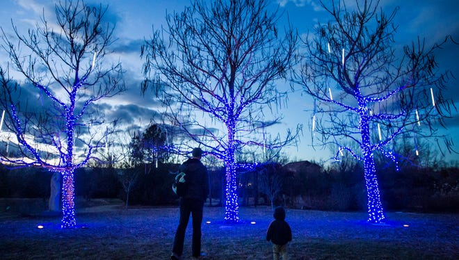 Jason Schultz and his son Grady, 2, check out some of the lights at sunset on Friday evening, Dec. 1, 2017, at the Gardens on Spring Creek's Garden of Lights in Fort Collins, Colo.