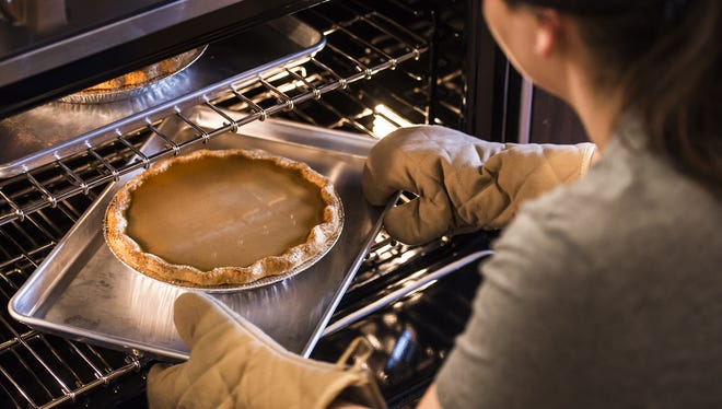 Head baker Rachel Brickel rotates pumpkin pies midway through baking on Friday, Nov. 17, 2017, at Ginger And Baker in Fort Collins, Colo.