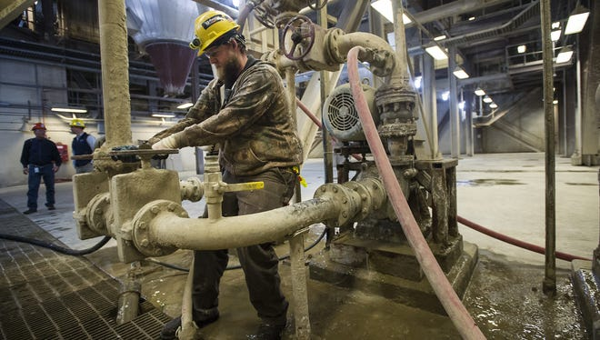 Plant operator Camron McCreery helps bring a system back online by opening and closing water valves on while taking instruction from the operating room on Tuesday, Nov. 14, 2017, in the scrubber building at the Rawhide Energy Station in Wellington, Colo.