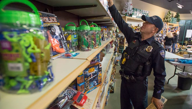 Fort Collins neighborhood enforcement team police officer Andy Leslie  picks out presents for underprivileged children with the Santa Cops of Larimer County on Wednesday, Dec. 6, 2017, at the Outlets at Loveland in Loveland, Colo.