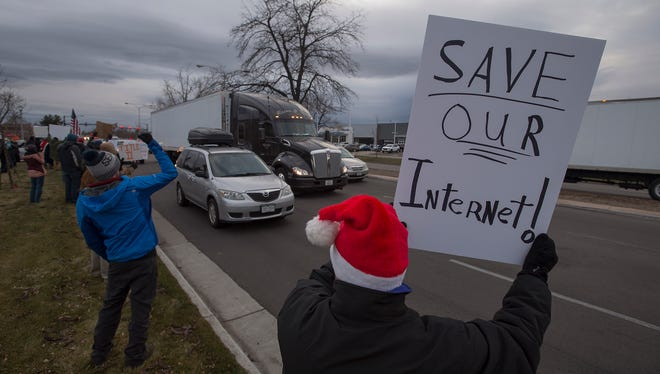 Windsor resident Guy Mendt holds a sign with other demonstrators in favor of continued net neutrality near peak traffic time on Thursday afternoon, Dec. 7, 2017, on South College Avenue in Fort Collins, Colo.