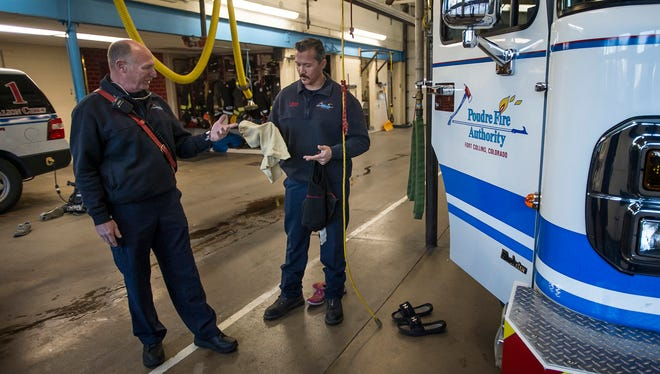 Safety officer Frank Dreckman and Capt. Dustin DeBaere show the differences between an older hood worn by firefighters and the newer version with added safety benefits on Thursday, Dec. 14, 2017, at the Poudre Fire Authority Station 1 in Fort Collins, Colo.