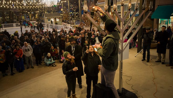 CSU senior economics student Daniel Golub, right, helps Gabriel Cohen, center, and Remy Kaskel lights the second to last branch during a Menorah Lighting & Chanukah Celebration on Sunday, Dec. 17, 2017, in Old Town Square in Fort Collins, Colo.