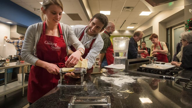 Liz Kaloupek, left, and Louis Narmour flatten out the dough for their pasta during a cooking class on Friday, Dec. 15, 2017, at The Cooking Studio on North College Avenue in Fort Collins, Colo.