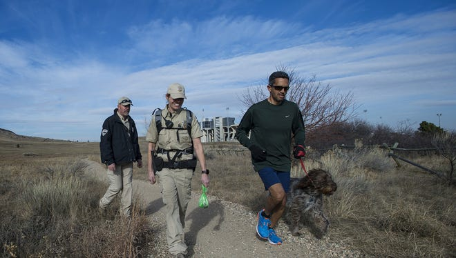 Fort Collins lead ranger Dave Irwin, left, and senior lead ranger Kristin Powell make room for a passing runner and his dog while walking the trail going past the old Hughes Stadium on Wednesday, Dec. 13, 2017, at Maxwell Natural Area in Fort collins, Colo.