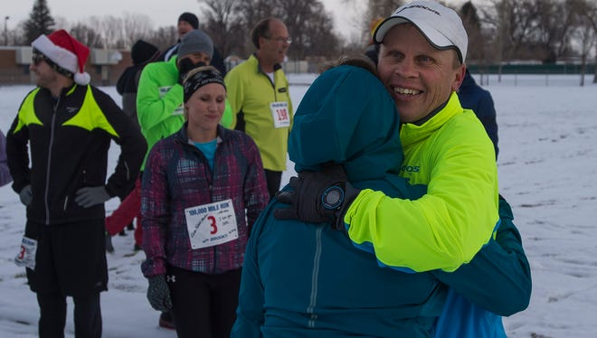 Kevin Follett hugs his wife Karen on Saturday after completing running his 100,000th mile to complete a lifetime goal. Follett, a semi-retired Fort Collins High School math teacher, has run an average of nearly 50 miles a week for 41 years.
