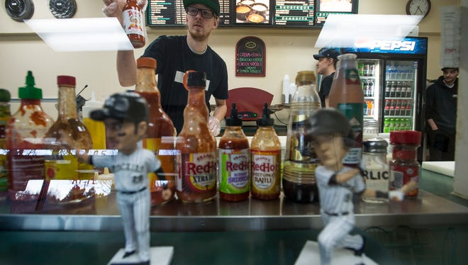 Obee's employee Austin Seward grabs hot sauce while making a sandwich on Tuesday, Jan. 2, 2018, at Obee's in Fort Collins, Colo.
