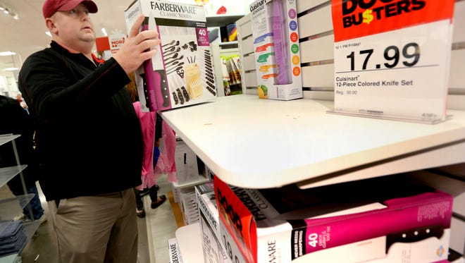 Lee Davis picks up one of the door buster items as she shops at JCPenny on Thanksgiving Day, Nov. 27, 2014.
