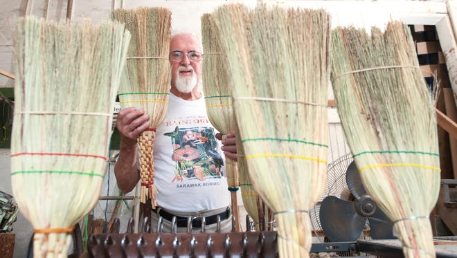 Sam Moyer of Mount Laurel, who has been in the broom-making business for more than 40 years, displays some of the brooms he has made recently. Moyer has a doctorate in genetics and taught biology for 25 years at Burlington County College in Pemberton.