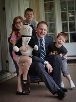 Matt Hearn wears a gray two-piece suit by Nautica; blue checked Charles Tyrwhitt shirt; black oxford dress shoes from Joseph Abboud with, from left, Josephine, 9, Charles, 12, and William, 6.