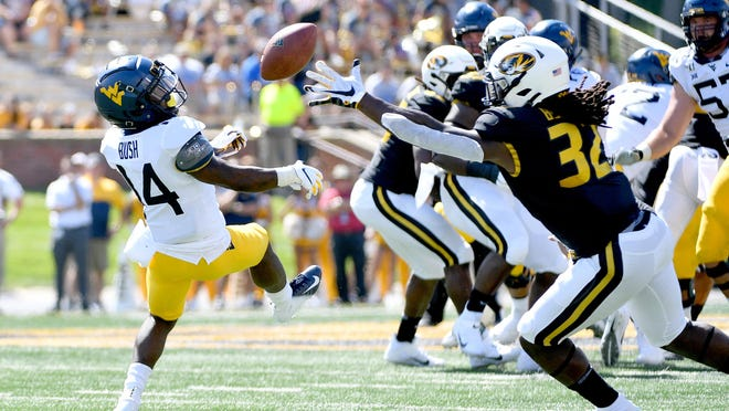 Missouri Tigers linebacker Nick Bolton (32) intercepts a pass meant for West Virginia Mountaineers wide receiver Tevin Bush (14) during the first half at Faurot Field in September 2019.