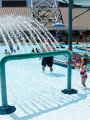 A little girl plays by a green arch jet at the Osborn Aquatic Center.