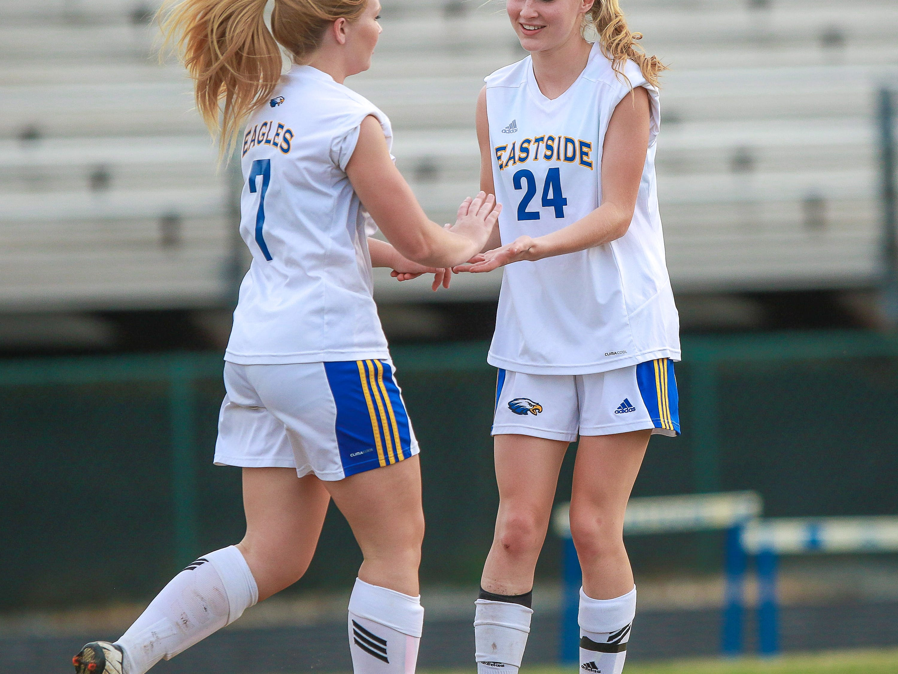 Asheton Robinson (7), left, celebrates with teammate Natalie Royaards (24) after scoring one of her three goals against Greer in the Eagles' 9-0 win Thursday night at John Carlisle Stadium.