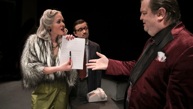 Billie Dawn (Heather Osteraa) shows Harry Brock (Scott Free) whose name is actually on the company's documents. Paul Verrall (Chuck Church) watches.
