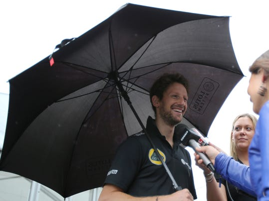 Lotus driver Romain Grosjean of France under an umbrella speaks to the media outside his hospitality suite at the Suzuka Circuit ahead of the Japanese Formula One Grand Prix in Suzuka, central Japan, Thursday, Sept. 24, 2015. (AP Photo/Toru Takahashi)