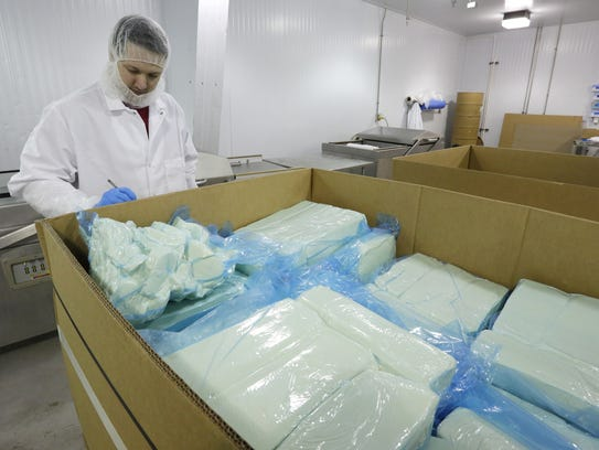 Eric Teska of Silver Creek documents the inspection and preparation loaves of mozzarella cheese for vacuum packing at Fairplay in Plymouth. Fairplay is a division of Titletown Cheese Trading Company.