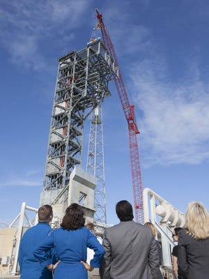 """Commercial Crew astronauts Bob Behnken and Suni Williams, along with employees of United Launch Alliance and other companies, watch as a crane lifts a 15-foot-long, 650-pound beam to the top of the Crew Access Tower during a """"topping off"""" ceremony Thursday."""