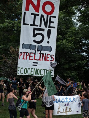 Demonstrators from Earth First protest outside the Midland, Mich., home of Michigan Attorney General Bill Schuette Wednesday July 6, 2016 to demand that Schuette take immediate action to shut down the Enbridge oil pipeline Line 5.