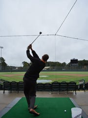 A golfer takes a swing at the first Par 3 at Perdue