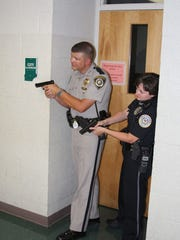 HPD Officer Jennifer Richmond (right) is one of several officers trained during a simulated mass shooting incident at Henderson County High School in 2008.